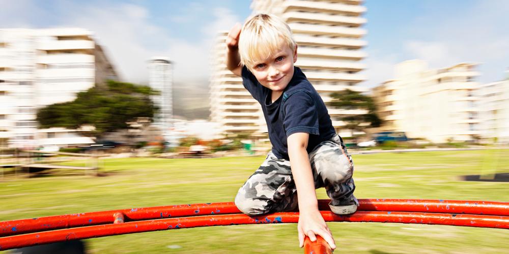 Boy on red play wheel